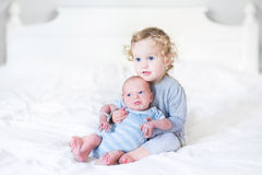 Schönes Kleinkindmädchen, das ihren neugeborenen Babybruder auf einem whi hält Stockfotografie