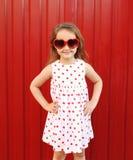 Schönes lächelndes Kind des kleinen Mädchens, das ein weißes Kleid und eine rote Sonnenbrille trägt Stockbilder