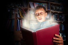 Schönes lustiges Kind, das ein großes Buch mit dem magischen Licht schaut überrascht hält Lizenzfreies Stockbild