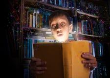 Schönes lustiges Kind, das ein großes Buch mit dem magischen Licht schaut überrascht hält Stockbild