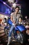 Schönes Mädchen, das auf einem blauen Motorrad, Stadtstraße am Nachthintergrund sitzt Stockbild