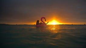 Schönes Mädchen, das aufblasbaren Flamingo in der Mitte von Ozean mit einem schönen Sonnenuntergang schwimmt stock footage