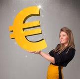 Schönes Mädchen, das ein großes Eurozeichen des Gold 3d hält Lizenzfreies Stockbild