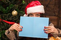 Schönes Mädchen, das eine neues Jahr- und Weihnachtspostkarte hält Stockbilder