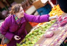 Schönes Mädchen, das Früchte am Fruchtmarkt wählt Lizenzfreie Stockbilder