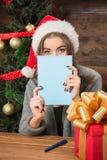 Schönes Mädchen, das hinter Postkarte des neuen Jahres und des Weihnachten sich versteckt Lizenzfreie Stockfotografie