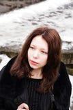 Schönes Mädchen, das ihre Zeit draußen im Winterpark genießt Stockfotografie