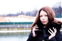 Schönes Mädchen, das ihre Zeit draußen im Winterpark genießt Stockbild