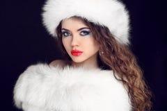 Schönes Mädchen, das im weißen Pelz-Mantel und im Pelzhut trägt. Winter W Stockbilder