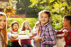 Schönes Mädchen, das kleinen Kuchen mit ihren Freunden hält Lizenzfreies Stockbild