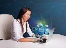 Schönes Mädchen, das am Schreibtisch sitzt und ein ihre Fotogalerie überwacht Lizenzfreie Stockbilder