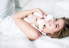 Schönes Mädchen, das in weißes Bett mit Bruin legt Stockbild
