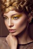 Schönes Mädchen in einem Goldkleid mit kreativem Make-up und Borten auf ihrem Kopf Die Schönheit des Gesichtes Lizenzfreies Stockbild