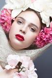 Schönes Mädchen in einem Kopftuch in der russischen Art, mit großen Blumen auf seinen Haupt- und roten Lippen Schönes lächelndes  Lizenzfreie Stockbilder
