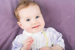 Schönes Mädchen in einem purpurroten Kleid auf einer gestrickten Decke Stockfotografie