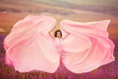 Schönes Mädchen in einem rosa Kleiderfliegen auf einem Lavendelgebiet Stockfotografie
