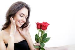 Schönes Mädchen empfängt drei rote Rosen Sie ist überrascht und betrachtet die Blumen und das Lächeln Stockfotografie