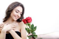 Schönes Mädchen empfängt drei rote Rosen Sie ist überrascht und betrachtet die Blumen und das Lächeln Stockbild