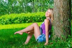 Schönes Mädchen im Denimoverall, der nahe einem Baum sitzt Stockfotografie