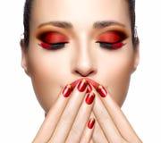 Schönes Mädchen im Rot mit den Händen auf ihrem Gesicht Nagel Kunst und Makeu Lizenzfreie Stockfotos