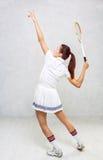 Schönes Mädchen im Tennis kleidet und an schwingt einen Tennisschläger Lizenzfreie Stockfotografie