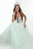 Schönes Mädchen mit dem langen Haar trägt luxuriöses Kleid und Krone Lizenzfreies Stockfoto