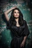 Schönes Mädchen mit dem Make-up, das gegen alte Wand mit der Schale der grünen Farbe aufwirft Hübscher Brunette im Schwarzen Attr Lizenzfreies Stockfoto
