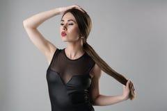 Schönes Mädchen mit den sexy Lippen, die im Bodysuit aufwerfen Stockbilder
