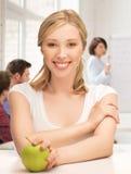Schönes Mädchen mit grünem Apfel in der Schule Lizenzfreies Stockfoto