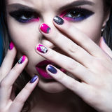Schönes Mädchen mit hellem kreativem Modemake-up und buntem Nagellack Kunstschönheitsdesign Stockfotos