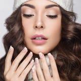 Schönes Mädchen mit leichtem Make-up, Designmaniküre und Lächeln im weißen Knithut Warmes Winterbild Schönes lächelndes Mädchen Lizenzfreies Stockbild