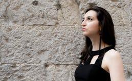 Schönes Mädchen mit schwarzem Kleid und den Ohrringen, die oben, Zementwand schauen Stockfotografie