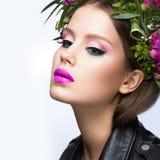 Schönes Mädchen mit vielen Blumen in ihrem Haar und in hellen rosa Make-up Eine Wiese mit blühenden Apfelbäumen Schönes lächelnde Stockbilder