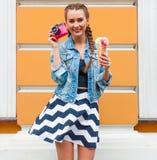 Schönes modernes junges Mädchen, das in einer Sommerkleider- und -denimjacke mit rosa Weinlesekamera und mehrfarbiger Eiscreme au Stockbilder