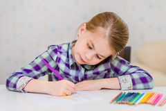 Schönes nachdenkliches kleines Mädchen mit dem blonden Haar, das bei Tisch sitzt und mit mehrfarbigen Bleistiften zeichnet Lizenzfreie Stockfotos
