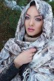 Schönes reizendes Mädchen, das unter Schnee in einem Schal und in einer warmen Strickjacke im Winterwald nahe den Bäumen steht Stockbilder