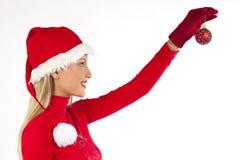 Schönes Sankt-Mädchen, das eine Weihnachtskugel anhält Lizenzfreie Stockfotos