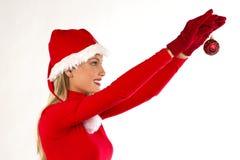 Schönes Sankt-Mädchen, das eine Weihnachtskugel anhält Lizenzfreies Stockfoto