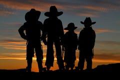 Schönes Schattenbild von vier jungen Cowboys mit einem Sonnenuntergang backgro Stockbild