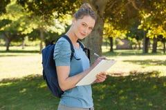 Schönes Schreiben der jungen Frau auf Klemmbrett am Park Stockbild