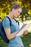 Schönes Schreiben der jungen Frau auf Klemmbrett am Park Stockfoto