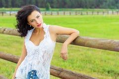 Schönes sexy Brunettemädchen mit den roten Lippen im weißen Hemd in den Denimkurzen hosen, die nahe der Pferdekoppel stehen Stockfotografie