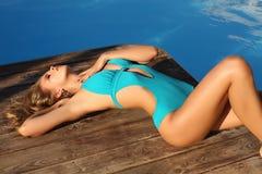 Schönes sexy gebräuntes Mädchen mit dem langen blonden Haar im eleganten Badeanzug Stockfotos