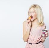 Schönes sexy herrliches blondes Mädchen mit hellem Make-up im rosa Kleid im Studio auf einem weißen Hintergrundsitzen Lizenzfreies Stockfoto
