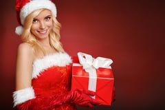 Schönes sexy Weihnachtsmann-Mädchen mit Geschenkbox. Stockbild