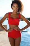 Schönes sinnliches Mädchen mit dem dunklen Haar trägt luxuriösen roten Badeanzug Lizenzfreies Stockbild