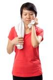 Schönes Sportmädchen mit dem Tuch und Schweiß, welche die Kamera ermüdet, erschöpft und verschwitzt nach Turnhallenübung betracht Stockfoto
