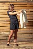 Schönes weibliches Modell, das weiße Jacke auf Fotoschießen überprüft Stockfotografie