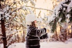 Schönes Winterporträt des Kindermädchens im sonnigen Winterwald spielt mit schneebedecktem Tannenzweig Stockfotografie