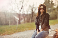 Schönheit in der Jacke und in Jeans, die in einem Park sitzen Lizenzfreies Stockbild